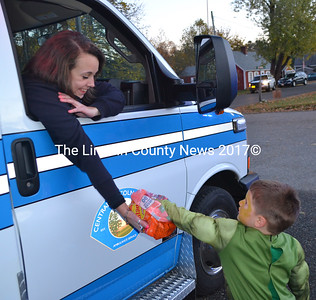 Madison Temple offers Sawyer Rogers some candy at the Damariscotta Police Department's trunk-or-treat event. (Maia Zewert photo)