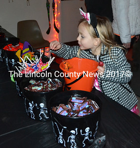 Evangeline Fraser, of Damariscotta, inspects a bucket of lollipops at the Newcastle Fire Station on Halloween, Monday, Oct. 31. The Newcastle Fire Department offered candy, cider, and donuts for visitors of all ages. (Maia Zewert photo)