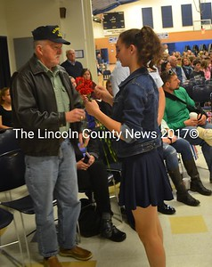 Medomak Middle School student Emily Harris presents a flower to veteran Richard Minzy to honor him for his service. (Abigail Adams photo)