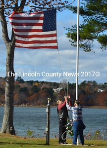 Gerald Miller (left) and Mike Johnson raise the American flag at Schooner Cove in Damariscotta the morning of Veterans Day, Friday, Nov. 11. Both Miller and Johnson are veterans of the U.S. Navy and members of The American Legion Wells-Hussey Post No. 42. (Maia Zewert photo)