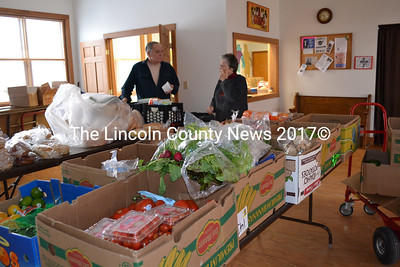 Help Yourself Shelf volunteers Robert Bickford and Nancy Roby look over donations to the pantry from Hannaford Supermarket and Shaw's. (Charlotte Boynton photo)