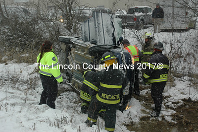 Members of the Newcastle and Damariscotta fire departments help free a Newcastle woman from her vehicle after it slid off the road on Mills Road in Newcastle on Monday afternoon, Feb. 8. Lincoln County Sheriff's Office Sgt. Matt Day said road conditions may have contributed to the accident. (Maia Zewert photo)