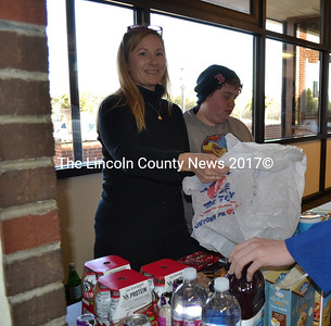 Wiscasset Middle High School teacher Hollie Paul holds out a bag to a Wiscasset student at the school's food pantry as student volunteer Ashley Lord looks on. St. Philip's Episcopal Church supplies the pantry. (Charlotte Boynton photo)