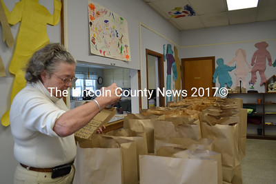 Help Yourself Shelf volunteer Anne Dill prepares bags for the clients who pick up food at the pantry each Thursday. (Charlotte Boynton photo)
