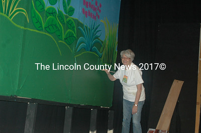 "Artist Mary Sue Weeks paints the huge flowers that will adorn the set of ""Iolanthe,"" which opens at the Lincoln Theater on Friday, March 18. Weeks has created the Fairyland for Act 1 of the Gilbert and Sullivan operetta and a skyline of London for Act 2, which takes place in the House of Parliament. (Eleanor Cade Busby photo)"