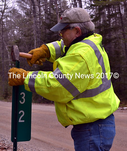 Westport Island Fire Chief Robert Mooney installs a sign on Coveside Way in Westport Island on Friday, March 4. Mooney estimates that one in 100 addresses on the island has a number easily visible from the road. (J.W. Oliver photo)