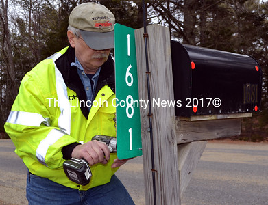 Westport Island Fire Chief Robert Mooney installs a sign on a mailbox post on Main Road in Westport Island on Friday, March 4. The reflective numbers are far more visible to firefighters and first responders than the numbers on the mailbox, especially at night or during a storm. (J.W. Oliver photo)