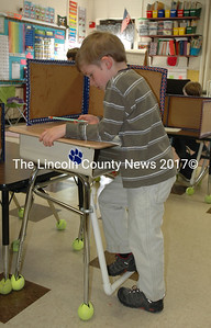Great Salt Bay Community School first-grader Ben Arnold works on an assignment while moving the fidget bar of his standing desk with his foot Monday, March 14. (Maia Zewert photo)