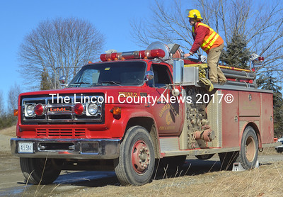 A firefighter works atop a Somerville engine at the scene of a brush fire off Crummett Mountain Road in Somerville the morning of Saturday, Feb. 27. (Alexander Violo photo)