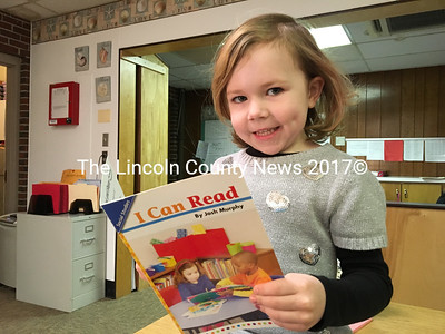 Charlotte Crawson, a kindergarten student at Wiscasset Elementary School, shows off her reading skills to Mrs. Collamore in the main office.