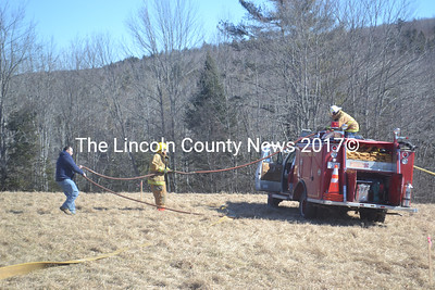 Firefighters work at the scene of a brush fire in Somerville on Saturday, Feb. 27. Somerville Fire Chief Mike Dostie said firefighters extinguished the brush fire in about an hour. (Alexander Violo photo)