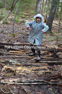 """Nine-year-old Emmeline Flewelling, a member of the Trail Blazers, is proud of her handiwork as one of the builders of a """"corduroy path"""" over a particularly wet spot in the trail in the woods behind Great Salt Bay Community School. (Christine LaPado-Breglia photo)"""