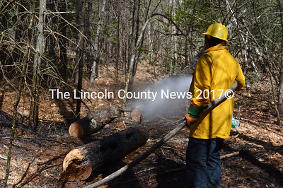 A firefighter sprays down a tree after a brush fire at 664 Benner Road in Bristol on Thursday, April 21. (Maia Zewert photo)