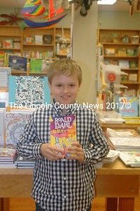 "Andrew Lyndaker holds a copy of ""Charlie and the Chocolate Factory"" by Roald Dahl at Sherman's Maine Coast Book Shop in Damariscotta. He was delighted to find the book the day before going to New York to audition for the part of Charlie in a new Broadway musical based on the book. (Eleanor Cade Busby photo)"