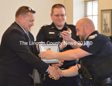 Damariscotta Police Chief Ron Young (left) presents Sgt. Jason Warlick with the 2015 Officer of the Year Award as Officer Jim Dotson looks on Wednesday, April 20. (Maia Zewert photo)