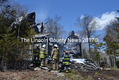 Fire officers survey the remains of a cottage in South Bristol on Saturday, May 14. (J.W. Oliver photo)