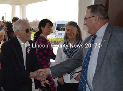 George Whitten (left) shakes hands with Maine Gov. Paul LePage while his daughter, Amy Whitten, looks on at the Boothbay Harbor Country Club on May 11. George Whitten, a World War II veteran, raised the flag during the ribbon-cutting ceremony. (Maia Zewert photo)