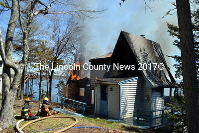 """Firefighters work at the scene of a cottage fire on Rutherford Island on Saturday, May 14. The fire was """"well out through the roof"""" before a neighbor saw and reported it, according to a fire official. (J.W. Oliver photo)"""