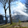 Firefighters blast the remains of a cottage on Miles Road in South Bristol in an attempt to extinguish a persistent fire Saturday, May 14. (J.W. Oliver photo)