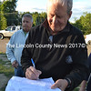 Damariscotta Planning Board member Bruce Garren signs Maine-ly Pawn owner Mark Hoffman's conditional use permit application during the board's site walk at the property Monday, June 14. (Maia Zewert photo)