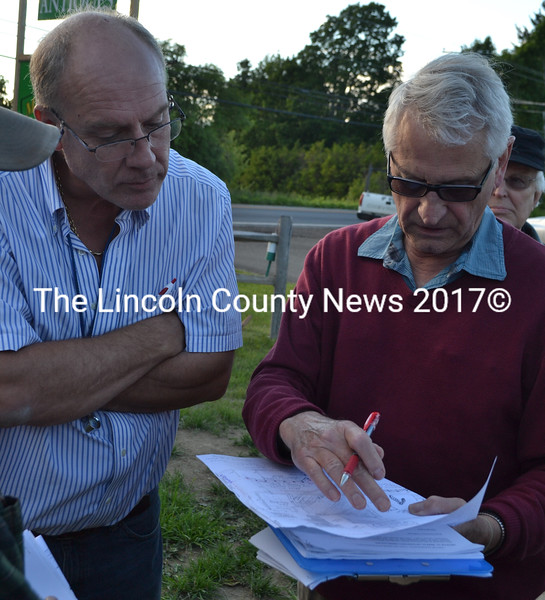 Maine-ly Pawn owner Mark Hoffman (left) and Damariscotta Town Planner Tony Dater study a map of the Maine-ly Pawn property during a Damariscotta Planning Board site walk of the Maine-ly Pawn property Monday, June 13. (Maia Zewert photo)