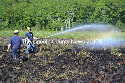 Bristol firefighters soak a marsh area off Carl Bailey Road the morning of Thursday, June 16 to extinguish any hot spots remaining after a fire the night before. (Maia Zewert photo)