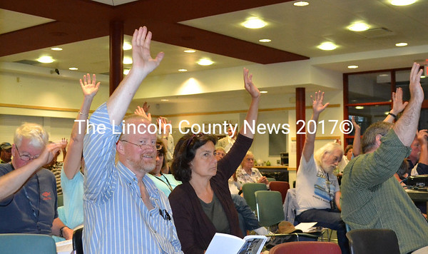 Voters, including Rob and Stephanie Nelson, approve an article during Newcastle's annual town meeting Monday, June 20 in the Lincoln Academy Alumni Dining Commons. Residents worked through the 26-article warrant in under 2 1/2 hours. (Maia Zewert photo)