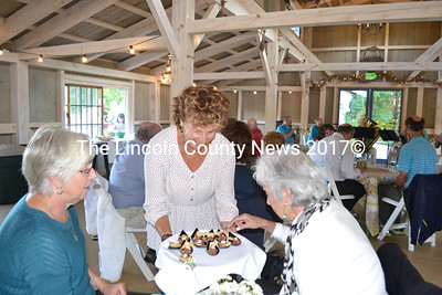 Michelle Peele (center) serves hors d'oeuvres to Carmen Tetu (left) and Betty Sawyer at the Bands for Books event. (Charlotte Boynton photo)