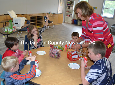 Terry Mitchell, the director of South Bristol School's new after-school program, serves snacks to the five children who attended the program Tuesday, Sept. 6. Clockwise from bottom left: South Bristol kindergartners Sam Kress and Autumn Cantillo, third-grader Maya Redonnett, kindergartner Robert Bennett, and third-grader Blake Gamage. (Maia Zewert photo)
