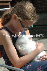 Alice Skiff holds one of the Great Salt Bay Community School agriculture club's rabbits in the courtyard of the school in September 2015. (Maia Zewert photo, LCN file)