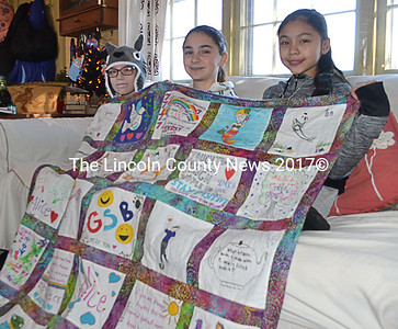 From left: Alice Skiff, Casey Nelson, and Sonny Cumming display a quilt, a gift from Great Salt Bay Community School students and staff to Alice, at the Skiffs' home in Newcastle. (Maia Zewert photo)