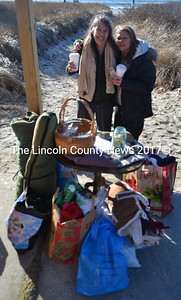 Pemaquid Polar Bear Dip founders Caryn Frosio (left) and Cindy Cheney pose behind some of the donations collected for the Lincoln County Animal Shelter during the event on New Year's Day. (Maia Zewert photo)