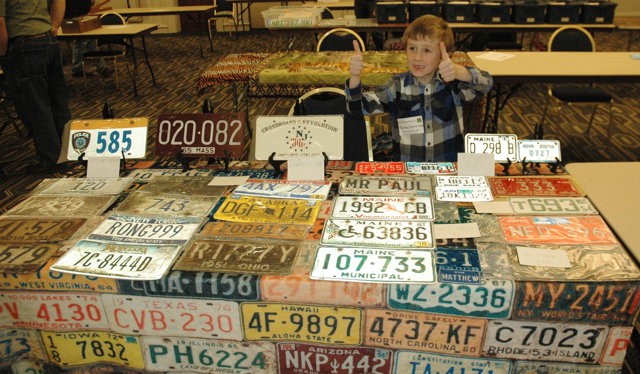 Mathew Roberts gives two thumbs-up by his license plate display at an Automobile License Plates Collectors Association meet in Massachusetts on Sunday, Nov. 12.