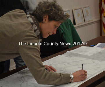 Newcastle Planning Board Chair Bonnie Stone signs a site plan from Mobius Inc. on Thursday, Feb. 16. The board unanimously approved Mobius' application to convert a house and barn into apartments at 21 Academy Hill Road. (Maia Zewert photo)