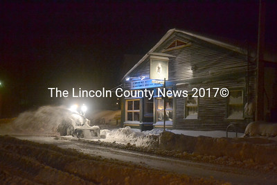 A Hagar Enterprises Inc. employee removes snow in front of S. Fernald's Country Store in downtown Damariscotta the evening of Tuesday, March 14. (Maia Zewert photo)