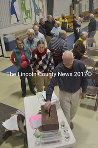 South Bristol residents wait in line to cast their ballots on an warrant article related to the education budget during the annual town meeting at South Bristol School on Thursday, March 16. (Maia Zewert photo)