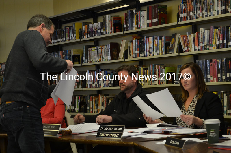 Wiscasset School Department Director of Facilities John Merry hands out budget information to Wiscasset School Committee Chair Michael Dunn and department Superintendent Heather Wilmot during a budget workshop Thursday, March 23. (Abigail Adams photo)