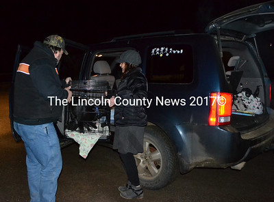 Christina Nelson (right) loads a crate of puppies into her vehicle with help from another volunteer with Underhound Railroad. After being rescued from high-kill shelters in the South, the dogs are transported to Maine, usually arriving in the middle of the night. (Maia Zewert photo)