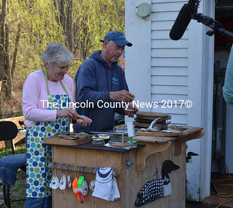 """Sharon and Leigh Morrill shuck oysters for the """"Maine Cabin Masters"""" film crew at their Newcastle home Friday, April 28. (Abigail Adams photo)"""