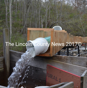 """Water pours from piping within the wooden chute the """"Maine Cabin Masters"""" replaced at the Damariscotta Mills fish ladder. (Abigail Adams photo)"""