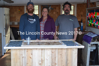 """From left: """"Maine Cabin Masters"""" Chase Morrill, Ashley Morrill-Eldridge, and Ryan Eldridge stand in front of a mobile shucking station built for a cabin at Glidden Point Oyster Farms on Friday, April 28. (Abigail Adams photo)"""