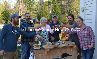 """From left: Chase Morrill, Adam Myer, Sharon and Leigh Morrill, Ryan Eldridge, and Ashley Morrill-Eldridge enjoy oysters at the Morrills' home after completing filming for """"Maine Cabin Masters"""" for the day Friday, April 28. (Abigail Adams photo)"""