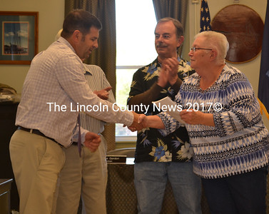 Former Wiscasset Parks and Recreation Director Todd Souza shakes Wiscasset Board of Selectmen Chair Judy Colby's hand after being presented with a town report at the selectmen's meeting Tuesday, May 16. (Abigail Adams photo)