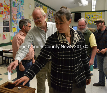 Newcastle residents Rob Nelson and Jenny Mayher cast their ballots for the town's secondary education budget during a special town meeting in the Great Salt Bay Community School cafeteria Wednesday, May 10. (Maia Zewert photo)