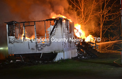 Flames rise from propane tanks behind a mobile home at Brookside Mobile Home Park in Waldoboro as firefighters work to prevent the spread of the fire to neighboring structures early Saturday, May 20. (Abigail Adams photo)