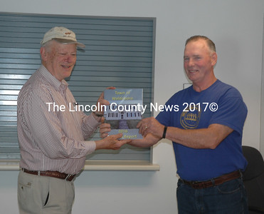 Waldoboro Board of Selectmen Chair Clinton Collamore (right) presents a copy of the town's 2016 annual report to Ted Wooster at the town office Wednesday, May 17. (Alexander Violo photo)