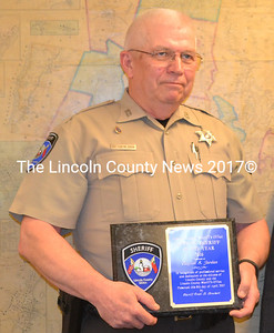 Lincoln County Sheriff's Deputy Clayton Jordan holds a plaque naming him 2016 Deputy Sheriff of the Year during a meeting of the Lincoln County Board of Commissioners on Tuesday, May 2. (Charlotte Boynton photo)