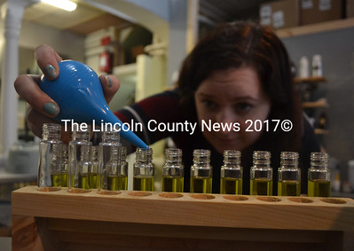 Long Winter Soap Co. employee Kat Rogers fills bottles of perfume at the company's new location at 11 Friendship St. in Waldoboro. Long Winter Soap Co. also sells soap, lip balm, body cream, and other body care products. (Maia Zewert photo)