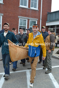 Dan Asher (front left) and Tobias Francis (front right) help Lincoln Academy students carry a 14-foot traditional Wabanaki birchbark canoe from the school in Newcastle to downtown Damariscotta on Thursday, April 27 for a launching ceremony at the Damariscotta River. (Christine LaPado-Breglia photo)