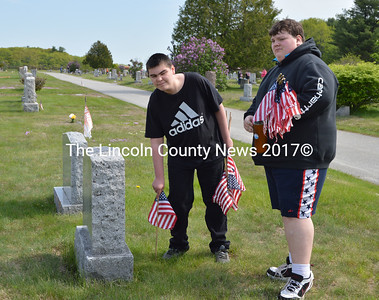 Whitefield students Ryan Williams (left) and Tyler Vaillancourt place flags on veterans' graves at the Mt. Hope Cemetery in Augusta. (Carrie Reynolds photo)